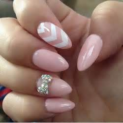 Baby pink almond nails with a studded bow and white chevron lines