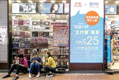 People Sit Next To An Advertisement For Alipay Operated By