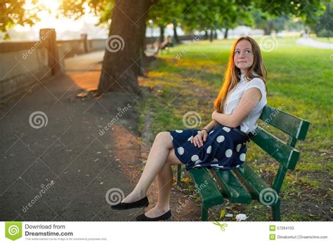 girl sitting on a bench cute girl with long golden hair sitting alone on a bench