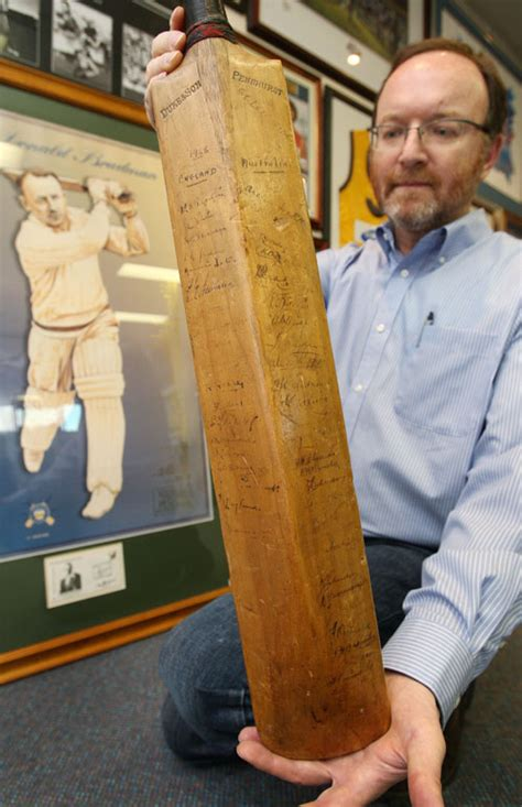 the bat the first auctioneer charles leski holds up the first cricket bat used by sir donald bradman in his test