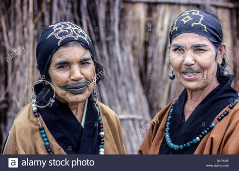 two elderly ainu women show off their traditional clothing