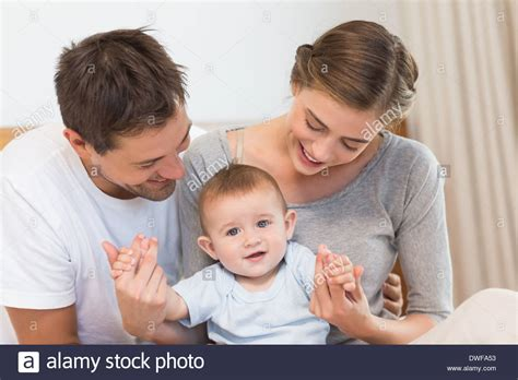 Bedroom Comforter happy parents with their cute baby son stock photo