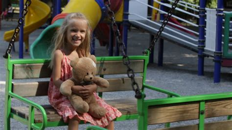 teddy plays on the swing child swinging girl playing with teddy bear toy at