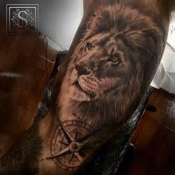 black and grey style lion tattoo on the right inner arm