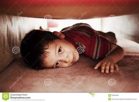 hiding under the bed kid hiding under bed stock photo image of playing game