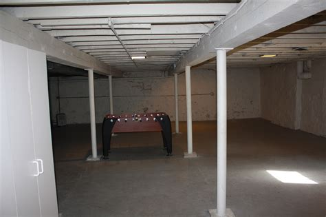 makeover basement house desgin painted with white color and wood ceiling beams ideas