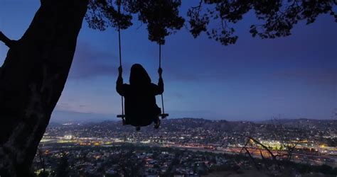 swing and the city man swinging on swings at night on top of mountain