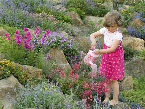 girl watering flowers cute girl watering the flowers flowers nature