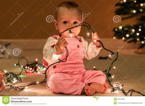baby with lights photo toddler with string of lights stock photo