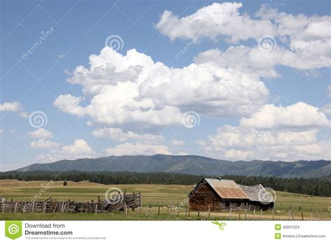 ranch log cabin wooden fence cumulus white clouds