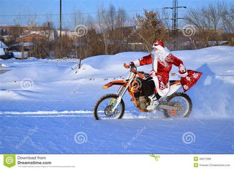 santa claus riding on a bike mx through deep snow stock