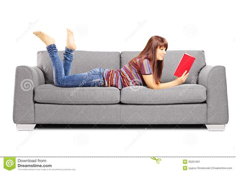 videos on the couch young female lying on a sofa and reading a book stock