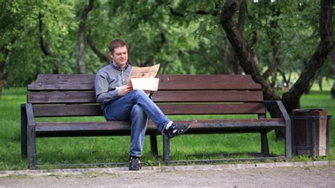 benching people man reads newspaper on bench in the park 1 by grey coast