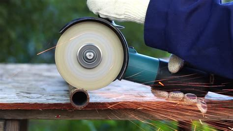 Worker In Gloves Cutting A Metal Pipe In Two Pieces With