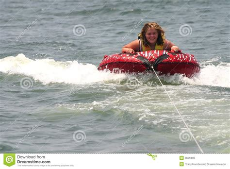inner tube pulled by boat blonde teenager being pulled on a inner tube raft stock