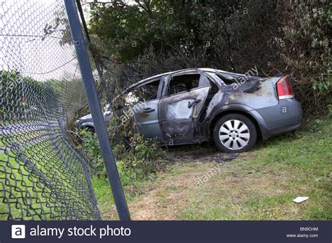 my car was stolen and crashed burned out stolen car crashed into a chain link fence in the uk stock photo royalty free image