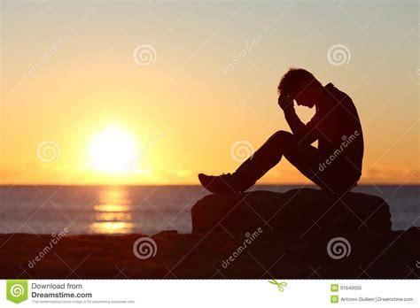 sun l for sad sad man silhouette worried on the beach stock photo