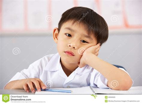 Unhappy Male Student Working At Desk In School Stock Photo Student Working At Desk