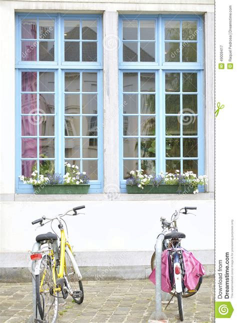 blue house with a blue window bicycles and white house with blue windows stock photo image 49009417