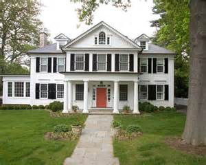 White house with black shutters and red door