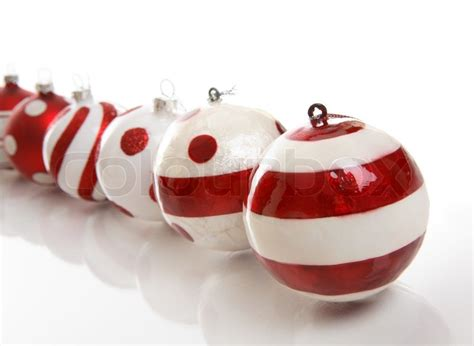 a selection of red and white christmas baubles on a white