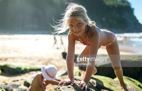 little girl models beach portrait of little girl climbing on a rock at the beach