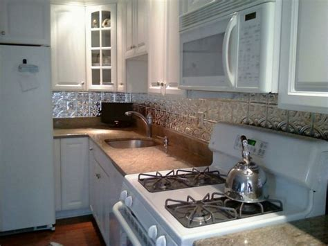 faux tin backsplash with white cabinets around the house