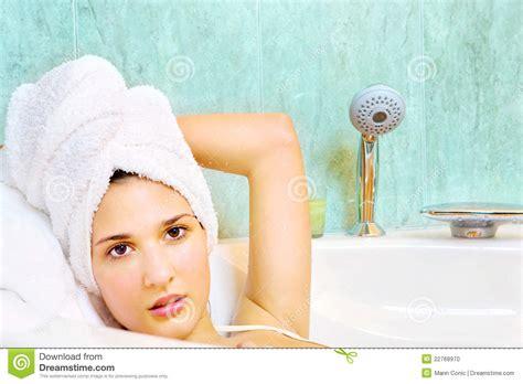 nella vasca da bagno donna con il tovagliolo sulla testa nella vasca da bagno