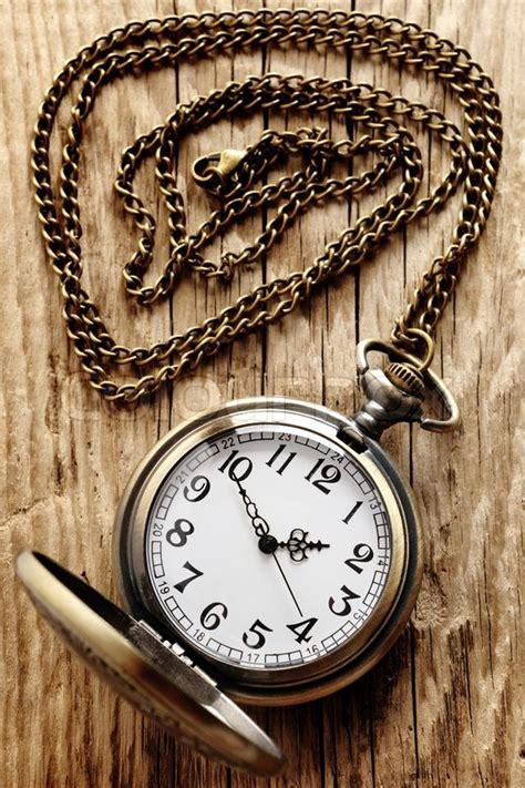 vintage pocket watch on chain on wooden background stock
