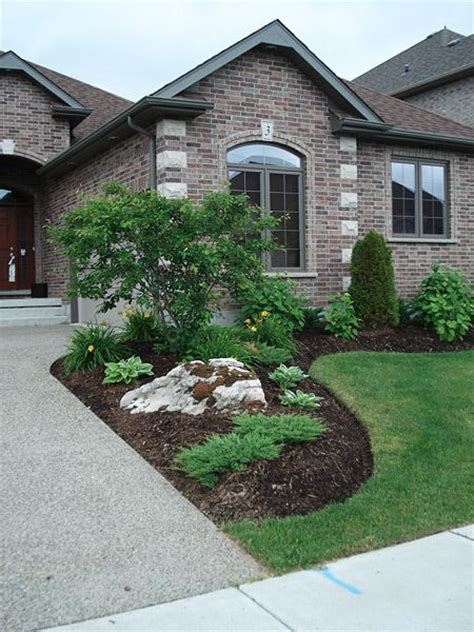 in my front yard simple planting with moss rock boulders landscaping