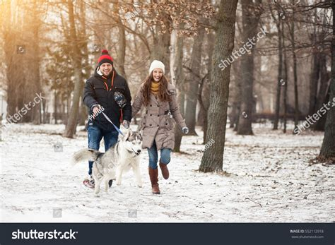 walking in a winter couple walking dog winter stock photo 552112918 shutterstock