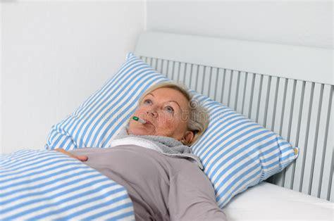 frau auf bett kranke frau die auf bett mit thermometer im mund liegt