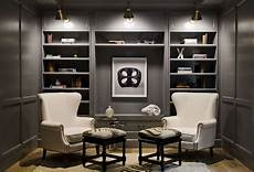 gray paneled den features a focal wall lined with gray built in shelves and cabinets illuminated