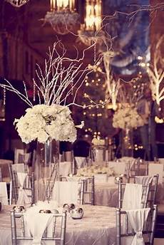 picture of a white and silver winter tablescape with silver candleholders a tall clear vase