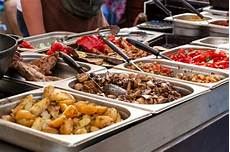 premium photo a counter with metal trays containing grilled food food and cooking equipment