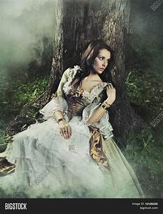 gorgeous brunette beauty in a old fashioned dress in a forest stock images bigstock