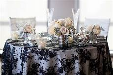 elegant wedding tablescape black lace overlay silver vases candles