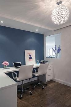 this modern home office features a white desk with two white desk chairs positioned in