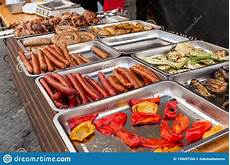 a counter with metal trays containing grilled sausages and meat food and cooking equipment at a