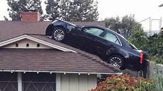 une voiture termine sa course sur le toit d une maison