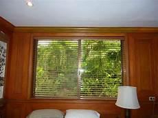 faux wood blinds mounted inside the headboard window frame
