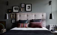 dark grey walls in a bedroom with hanging bedside lights accents of pink and burgundy lighten