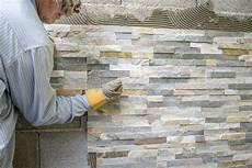 oudere mens die een muur met siertegels verfraaien stock
