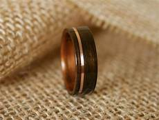 men s wooden wedding band with 14k rose gold inlay in macassar ebony wood with koa wood lining