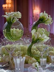 white calla lilies curled into circular glass vases make a striking and appealing centerpiece