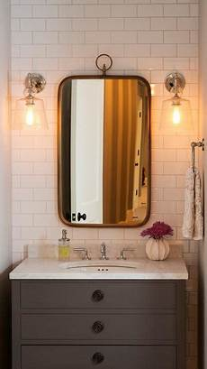 gray single washstand with curved brass mirror transitional bathroom