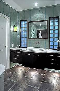 green glass tiled wall light countertop sink dark vanity under vanity lit medium dark tiled