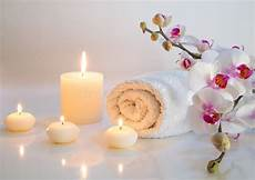 massaggio con le candele preparation for bath in white with towels candles and