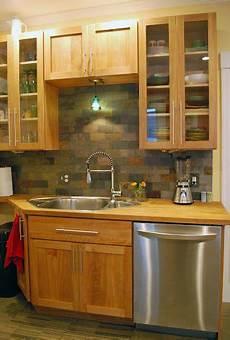 birch cabinets with a slate tile backsplash and