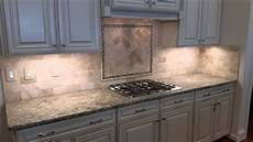 travertine backsplash with herringbone inlay